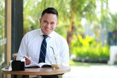 Biznesmen czyta książkę podczas kawowej przerwy Fotografia Royalty Free