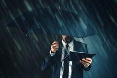 Biznesmen czytelnicza wiadomości gospodarcze na cyfrowej pastylce w deszczu zdjęcia stock