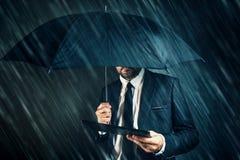 Biznesmen czytelnicza wiadomości gospodarcze na cyfrowej pastylce w deszczu obrazy royalty free