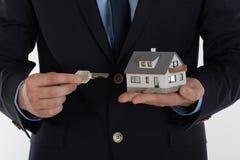 Biznesmen daje kluczowi i trzyma małego dom Obraz Stock