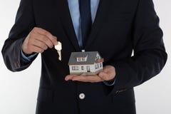 Biznesmen daje kluczowi i trzyma małego dom Zdjęcia Royalty Free