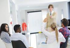 Biznesmen daje prezentaci jego koledzy przy pracy pozycją przed flipchart Zdjęcie Royalty Free