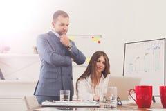 Biznesmen dogląda jego żeńską pomocniczą ` s pracę na laptopie co Obraz Royalty Free
