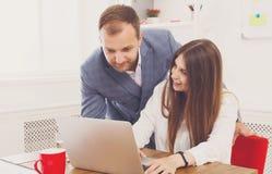 Biznesmen dogląda jego żeńskiego assistant& x27; s praca na laptopie Zdjęcia Stock