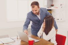 Biznesmen dogląda jego żeńskiego assistant& x27; s praca na laptopie Obrazy Stock
