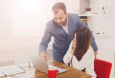 Biznesmen dogląda jego żeńskiego assistant& x27; s praca na laptopie Zdjęcie Stock
