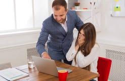 Biznesmen dogląda jego żeńskiego assistant& x27; s praca na laptopie co Zdjęcia Royalty Free