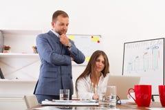Biznesmen dogląda jego żeńskiego assistant& x27; s praca na laptopie co Zdjęcie Royalty Free