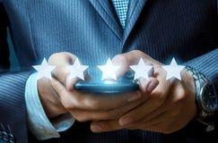 Biznesmen dotyka ekran jego telefon komórkowy z linią gwiazdowi symbole w przedpolu obraz stock