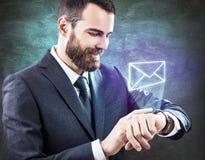 Biznesmen dotyka wirtualną ikonę od smartwatch Fotografia Royalty Free