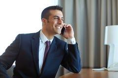 Biznesmen dzwoni na smartphone przy pokojem hotelowym Obrazy Royalty Free