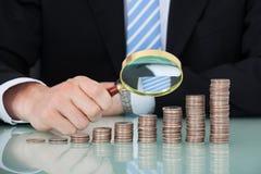 Biznesmen egzamininuje monety brogować jako prętowy wykres Fotografia Stock