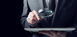 Biznesmen egzamininuje pastylkę z powiększać - szkło Pojęcie internet ochrona obraz royalty free