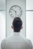 Biznesmen gapi się przy zegarem Fotografia Royalty Free