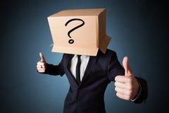 Biznesmen gestykuluje z kartonem na jego głowie z ques Fotografia Royalty Free