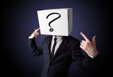 Biznesmen gestykuluje z kartonem na jego głowie z ques Obrazy Royalty Free