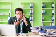 Biznesmen gniewny z przesadnym pracy obsiadaniem w biurze fotografia royalty free