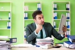 Biznesmen gniewny z przesadnym pracy obsiadaniem w biurze zdjęcie stock