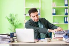 Biznesmen gniewny z przesadnym pracy obsiadaniem w biurze zdjęcia royalty free