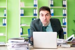 Biznesmen gniewny z przesadnym pracy obsiadaniem w biurze obraz stock