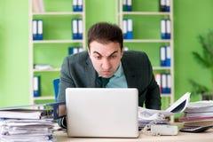 Biznesmen gniewny z przesadnym pracy obsiadaniem w biurze obraz royalty free