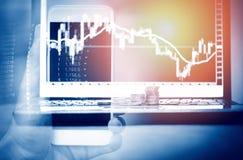 Biznesmen handluje online rynki walutowych używa smartphone lub giełda papierów wartościowych rynku deski dane ekranizują wiszącą fotografia royalty free