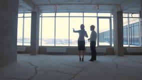 Biznesmen i biznesowa kobieta w kostiumu, ciężki kapelusz w nowym niedokończonym budynku biurowym komunikujemy, dyskutujemy, proj zdjęcie wideo