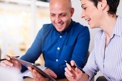 Biznesmen i bizneswoman kolaboruje na ich opóźnionym projekcie używać pastylkę obraz stock