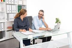 Biznesmen i bizneswoman pracuje wpólnie w biurze obrazy stock