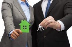 Biznesmen i bizneswoman trzyma zielonego dom fotografia royalty free