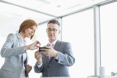Biznesmen i bizneswoman używa komórek ludzi w biurze Zdjęcia Royalty Free