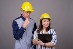 Biznesmen i dojrzały Azjatycki bizneswoman jest ubranym hardhat zdjęcia stock
