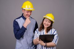 Biznesmen i dojrzały Azjatycki bizneswoman jest ubranym hardhat zdjęcie stock