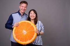 Biznesmen i dojrzały Azjatycki bizneswoman trzyma dużego pomarańczowego plasterek obrazy royalty free