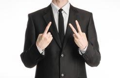 Biznesmen i gesta temat: mężczyzna w czarnym kostiumu z krawatem pokazuje znaka z jego prawą ręką i lewa ręka znaka dwa na t Zdjęcia Royalty Free
