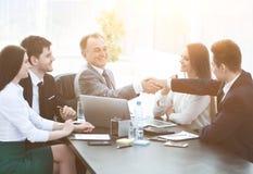 Biznesmen i inwestor trząść ręki przy stołem negocjacyjnym zdjęcia stock