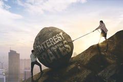 Biznesmen i kobieta ciągnie kamień obraz stock