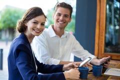 Biznesmen i kobieta używa przy kontuarem telefon komórkowego i cyfrową pastylkę zdjęcia stock