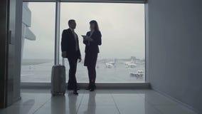 Biznesmen i lotnisko pracownik opowiadamy blisko okno zbiory