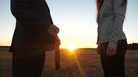 Biznesmen i młoda biznesowa kobieta robić rozdajemy, przechodzimy czarną teczkę do siebie i trząść ręki przy zmierzchem w, zdjęcie wideo