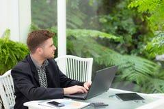 biznesmen i ono uśmiecha się, gdy pracuje na jego laptopie Obrazy Stock