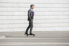 Biznesmen jeździć na deskorolce na ulicie zdjęcie stock