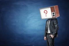 Biznesmen jeden rękę w kieszeni i głowie zamieniających olejem TV z znakiem zapytania na ekranie Zdjęcia Royalty Free