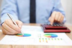 Biznesmen jest analizować raportowy i używać kalkulatora Obraz Royalty Free