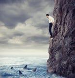 Biznesmen jest prawdopodobny spadać w morze z rekinem Ryzyko i szykany pojęcie zdjęcia stock