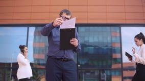 Biznesmen jest przyglądającymi pracującymi papierami podczas gdy dwa biznesowej dziewczyny chodzą za on 4K zdjęcie wideo