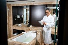 Biznesmen jest ubranym bathrobe w hotelowej łazience, używać jego cyfrową pastylkę podczas gdy stojący zdjęcia stock