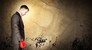 Biznesmen jest ubranym bokserskie rękawiczki i patrzeje smutny obrazy stock
