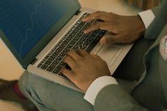 Biznesmen jest ubranym kostiumu mienia laptop na jego podołku i patrzeje w bankowość mapy zdjęcie royalty free