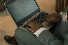 Biznesmen jest ubranym kostiumu mienia laptop na jego podołku i patrzeje w bankowość mapy fotografia royalty free